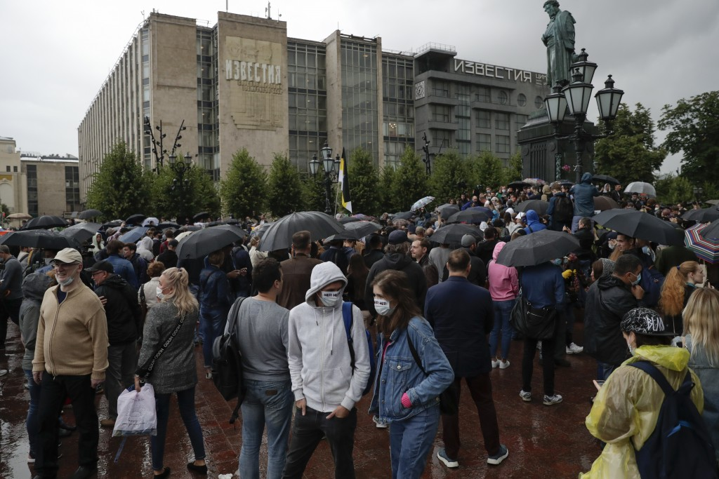 People gather to collect signatures on the results of voting on amendments to the Constitution in Pushkin Square, with a Pushkin monument in the backg...