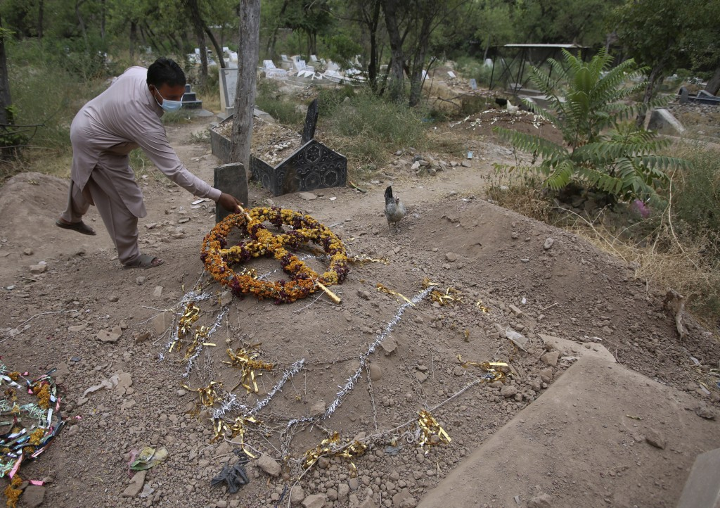 Yasir Lal, a Christian lays a wreath on the grave of his Nadeem Jordon who was killed by gunmen because he rented in a Muslim neighborhood, at a cemet...