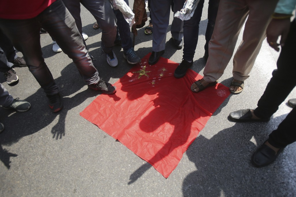 FILE - In this June 17, 2020, file photo, Indians stamp on the Chinese national flag during a protest against the Chinese government in Jammu, India. ...