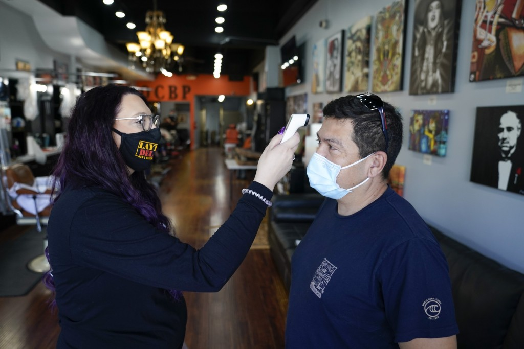 Rudy Pulido has his temperature checked by Melissa Acosta before he had his hair cut at Orange County Barbers Parlor on Wednesday, July 15, 2020, in H...