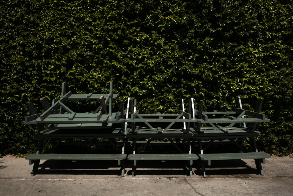 Picnic tables and benches are stacked up against a wall outside a bar temporarily closed due to the coronavirus pandemic, Wednesday, July 8, 2020, in ...