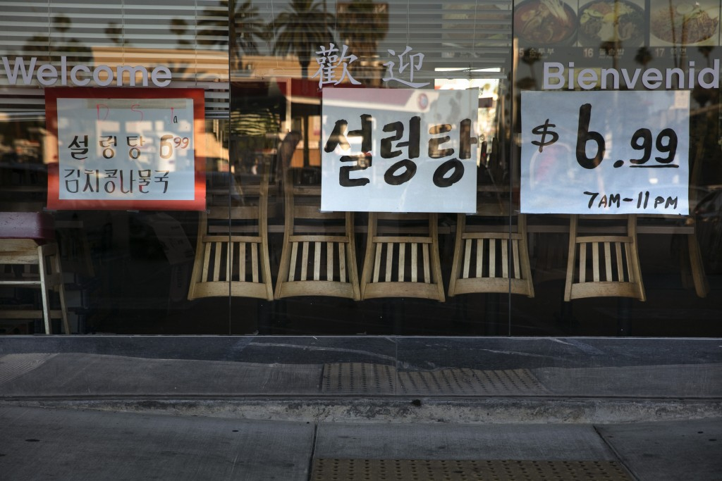 Chairs are flipped over on dining tables as featured menu items are posted on the window of a Korean restaurant open for takeout only due to the coron...