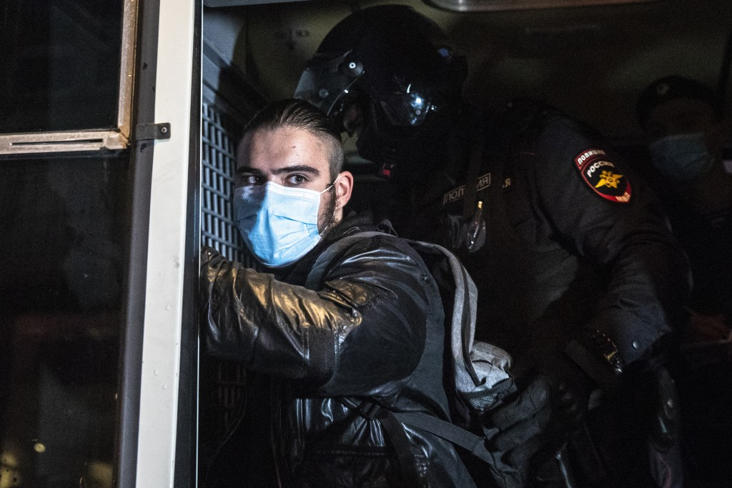 A police officer checks a protester after detaining him during a rally to cancel the results of voting on amendments to the Constitution in Petrovka s...