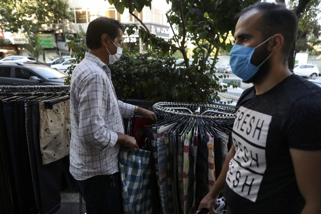 A vendor wearing a protective face mask to help prevent the spread of the coronavirus adjusts his items as a pedestrian walks past on a commercial str...