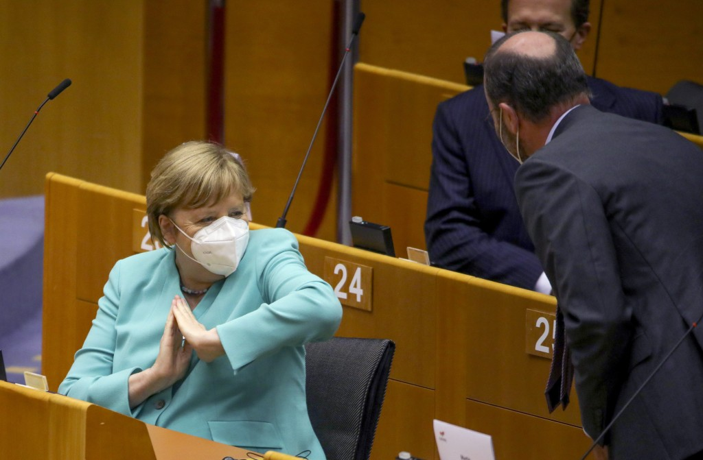FILE - In this Wednesday, July 8, 2020 file photo, German Chancellor Angela Merkel, left, offers an elbow to gesture hello as she attends a plenary se...