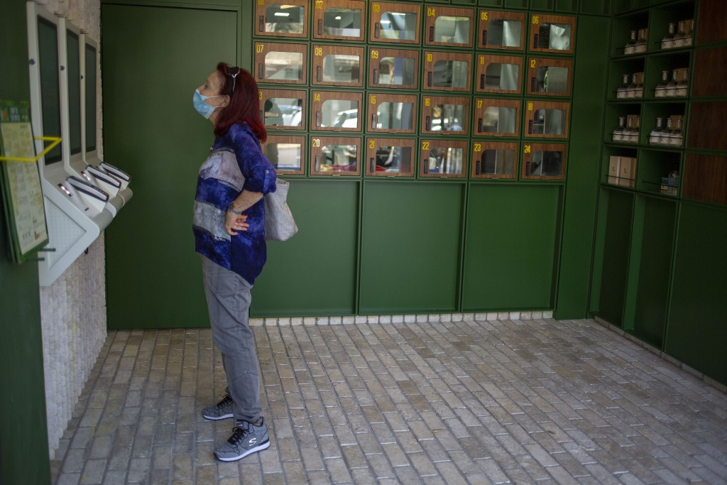 A customer reads the menu at Go noodles, where her order will be served in one of the glass-paned lockers seen behind her in Tel Aviv, Israel, Thursda...