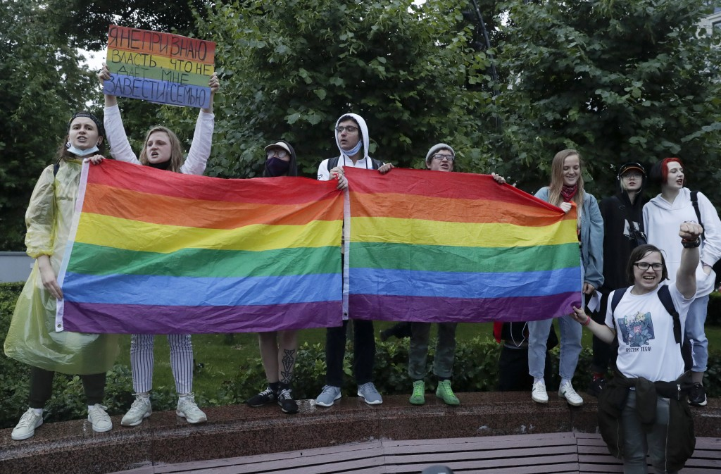 LGBT activists hold their flags at a rally to collect signatures to cancel the results of voting on amendments to the Constitution in Pushkin Square i...