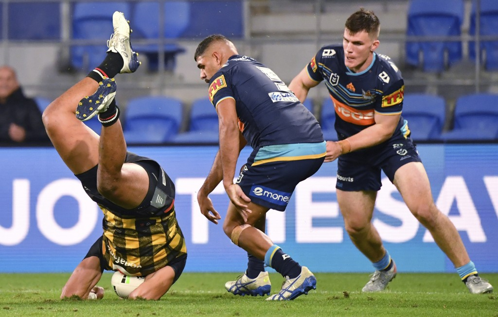 David Fusitu'a, left, of the Warriors falls to the ground after taking the high ball against Treymain Spry, centre, of the Titans during their Nationa...