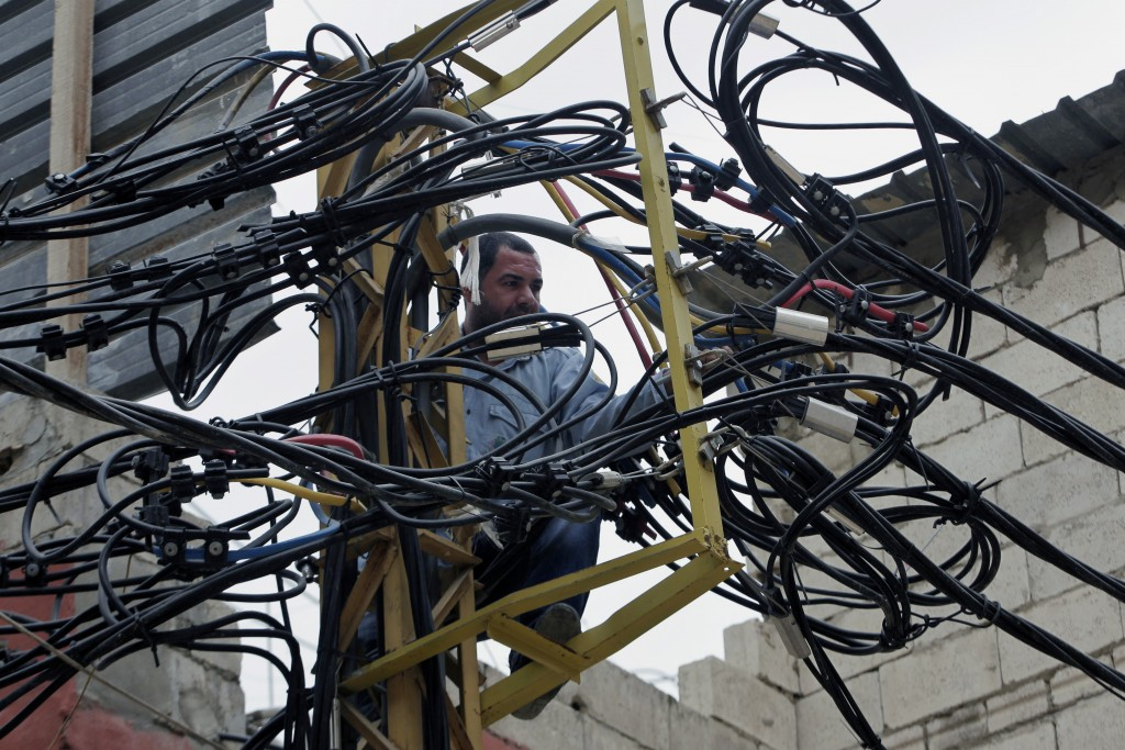 FILE - In this May 21, 2014, file, photo, Abu Wadiyeh, a 34-year-old Palestinian who was born in Syria, fixes power cables at the Palestinian refugee ...