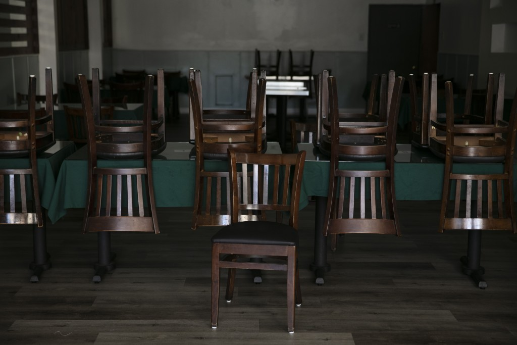 Chairs are stacked up on tables at a Peruvian restaurant open for takeout only due to the coronavirus pandemic Monday, July 6, 2020, in Los Angeles. (...