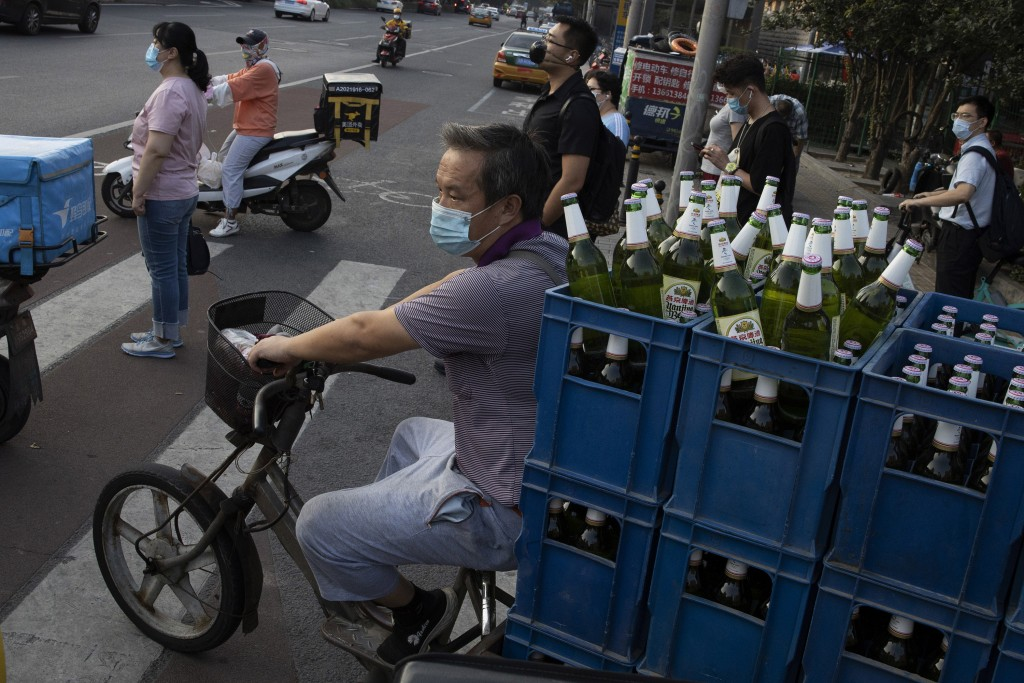 A delivery man transports beer on the streets of Beijing on Tuesday, July 14, 2020. China's economy rebounded from a painful contraction to grow by 3....