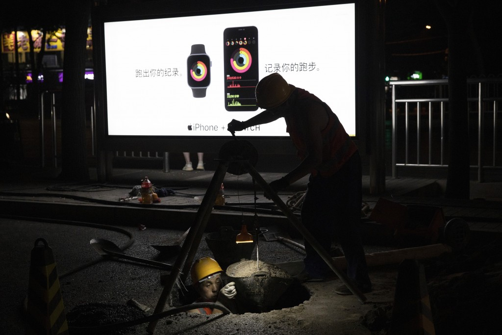 A worker hauls earth from a hole in the ground near advertisement for tech products in Beijing on Tuesday, July 14, 2020. China's economy rebounded fr...
