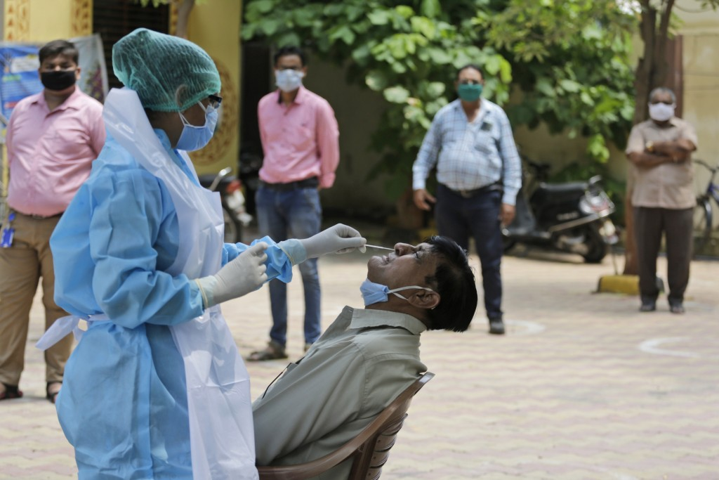 A health worker takes a nasal swab sample of a man at an urban health centre in Ahmedabad, India, Thursday, July 16, 2020. India's virus cases surged ...