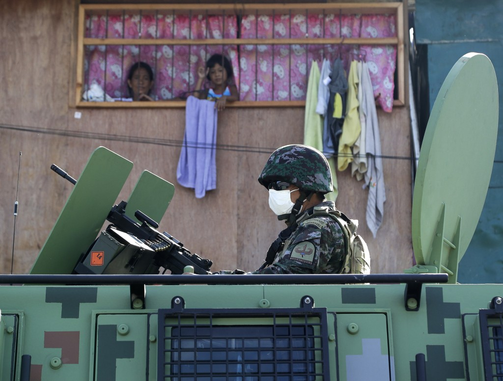 Residents watch as a police officer rides atop an Armored Personnel Carrier by their home during the start of a lockdown due to a rise in COVID cases ...