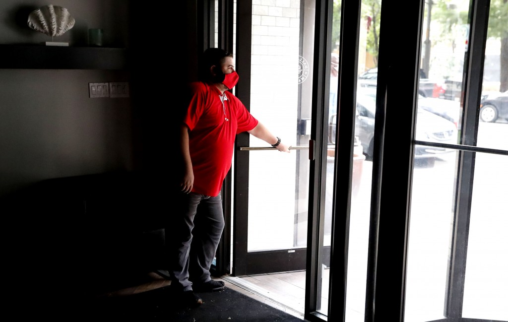 Wearing a mask amid concerns of the spread of the coronavirus, Dimitris Anagnostis opens the door to Chop House Burgers before the restaurant opened i...