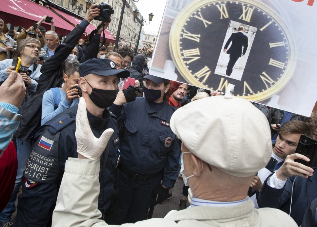 A protester argues with a policeman during a rally to protest against the results of voting on amendments to the Constitution in St. Petersburg, Russi...
