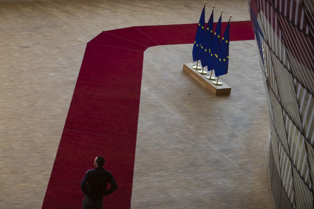 A man walks along a red carpet intended for the arrival of EU leaders at the European Council building in Brussels, Thursday, July 16, 2020. On Friday...