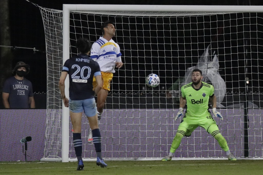 Vancouver Whitecaps goalkeeper Maxime Crepeau, right, reacts as San Jose Earthquakes forward Chris Wondolowski, second from left, heads the ball for a...