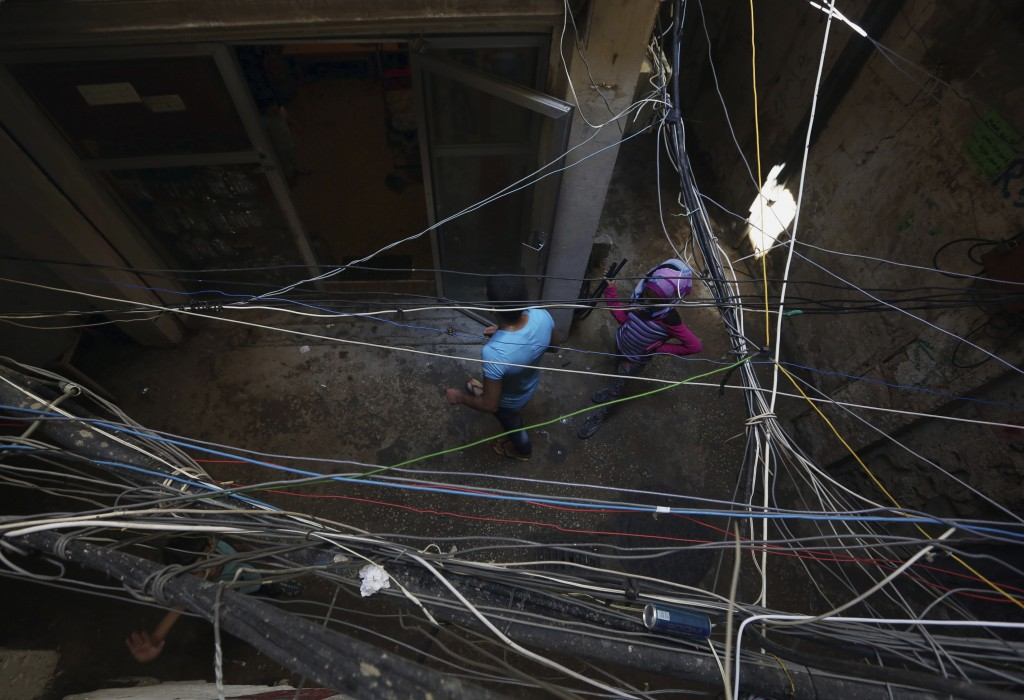 FILE - In this May 24, 2014, file, photo, Palestinian refugees walk under electricity cables in an alley in the Palestinian refugee camp of Shatila in...