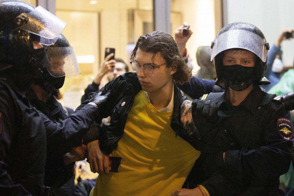 Police officers detain a protester during a rally to cancel the results of voting on amendments to the Constitution in Moscow, Russia, Wednesday, July...