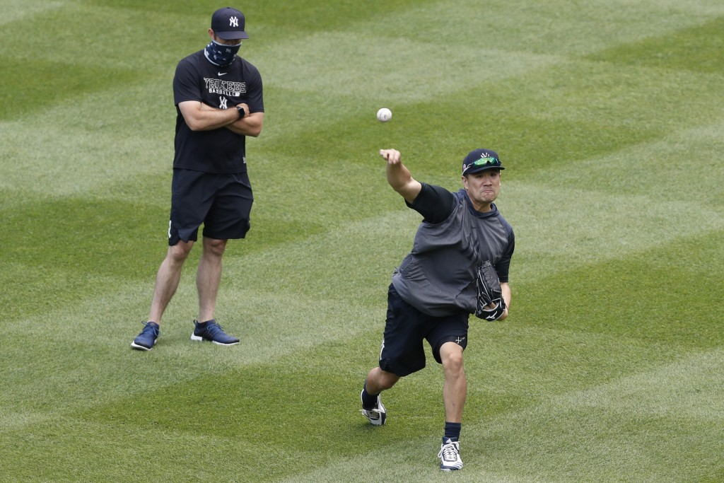 New York Yankees pitching coach Matt Blake, left, watches starting pitcher Masahiro Tanaka throw in the outfield at the Yankees summer baseball traini...