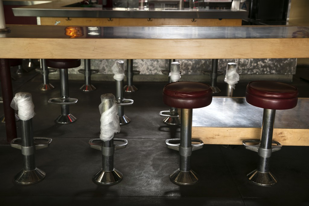 Bar stool seats are removed for social distancing at a bar temporarily closed due to the coronavirus pandemic Wednesday, July 8, 2020, in Los Angeles....