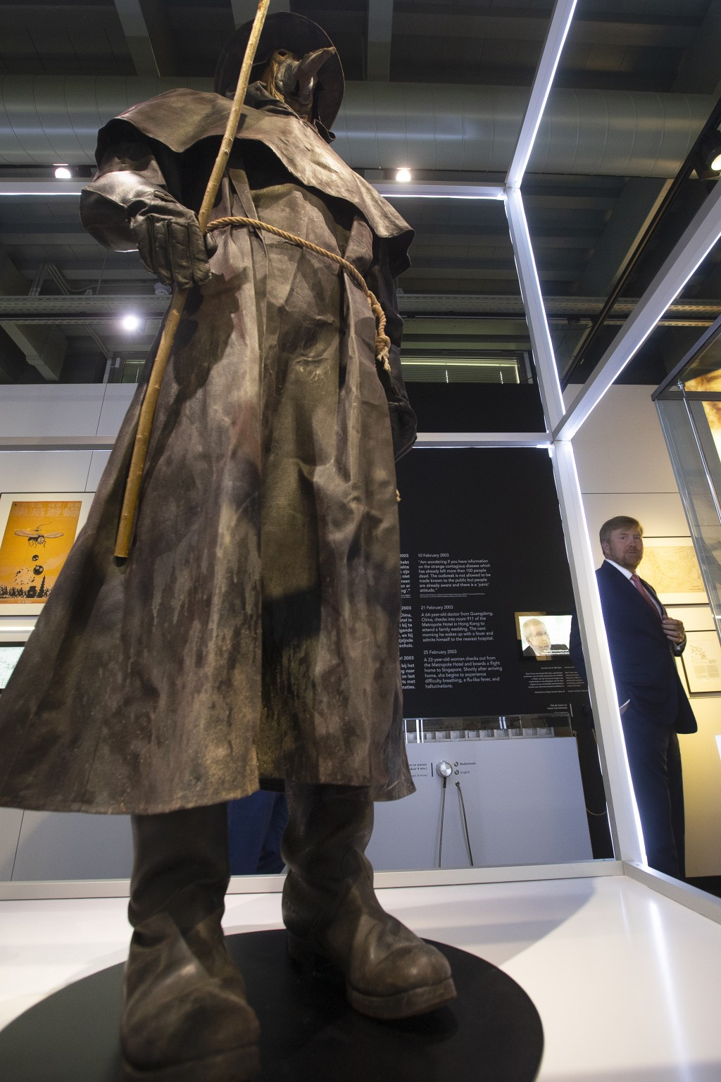 """Dutch King Willem-Alexander, rear right, looks at a replica of a plague doctor's long robe as he tours the """"Contagious!"""" exhibit at Rijksmuseum Boerha..."""