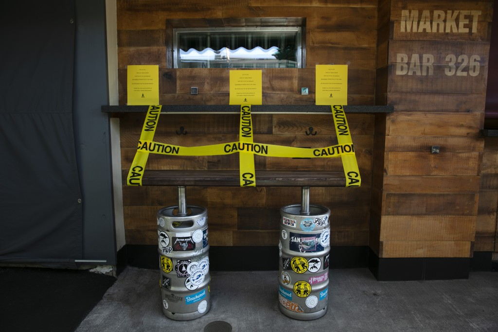 A bench made with kegs is taped off to prevent people from sitting at a bar temporarily closed due to the coronavirus pandemic Wednesday, July 8, 2020...