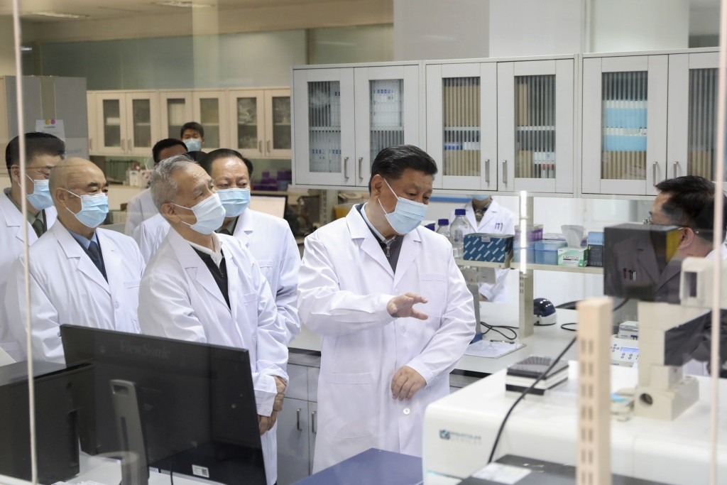 In this March 2, 2020, photo released by Xinhua News Agency, Chinese President Xi Jinping learns about the progress on the research into COVID-19 vacc...