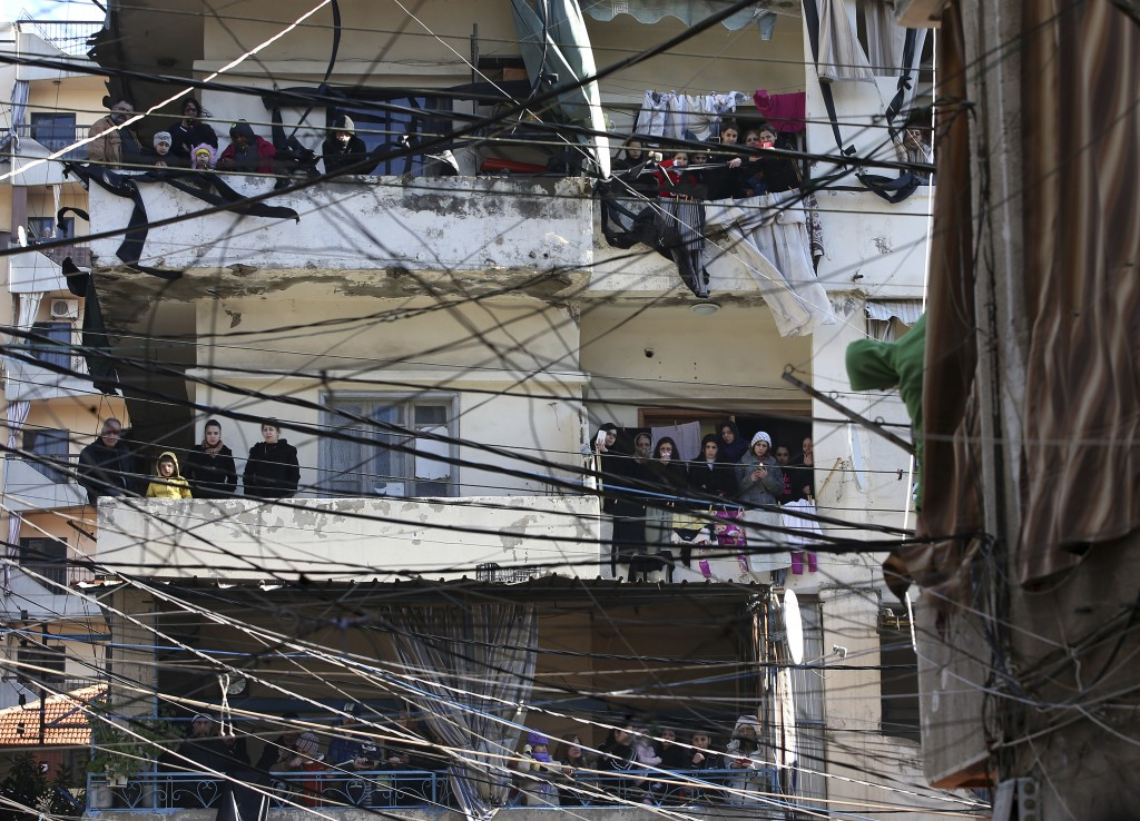 FILE - In this Jan. 11, 2015, file, photo, Alawite mourners seen through electricity wires stand on their balconies watching the funeral procession of...