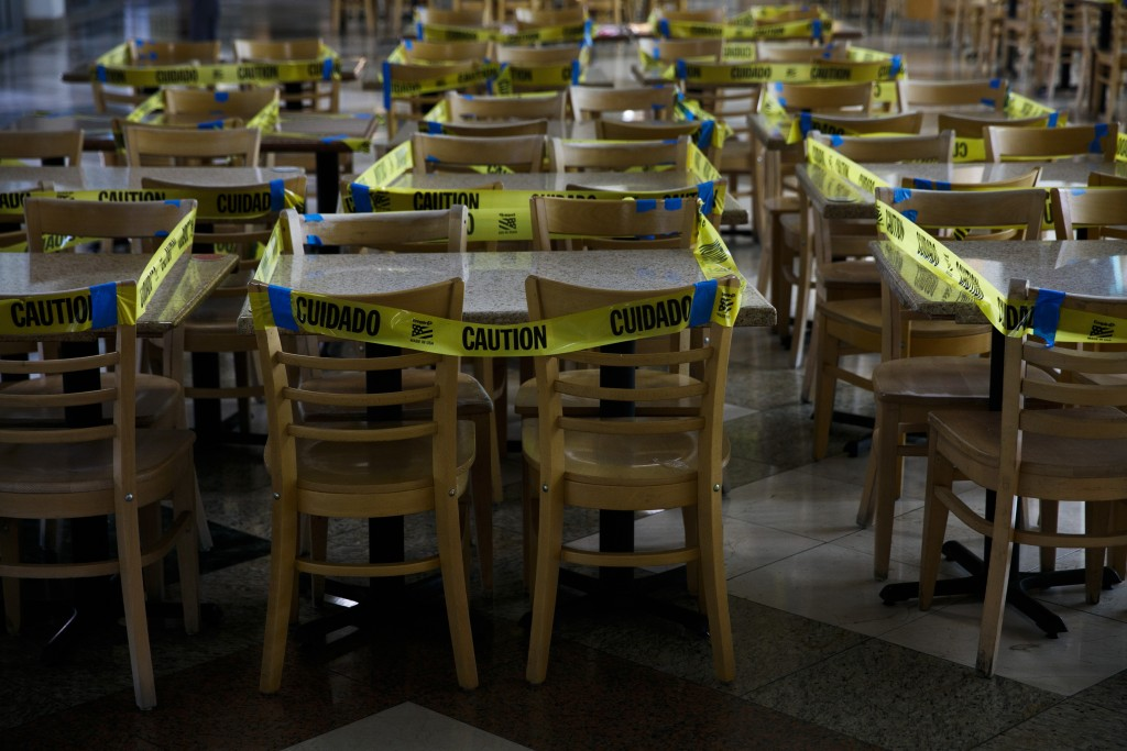 Caution tape is wrapped around dining tables and chairs at a food court to prevent indoor dining due to the coronavirus pandemic in the Koreatown sect...