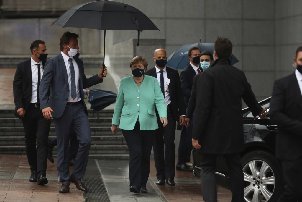 FILE- In this Wednesday, July 8, 2020 file photo, German Chancellor Angela Merkel, center, walks under an umbrella as she leaves, after addressing a p...