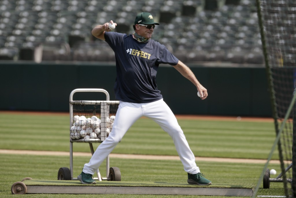 Oakland Athletics manager Bob Melvin pitches during baseball practice Wednesday, July 15, 2020, in Oakland, Calif. (AP Photo/Ben Margot)