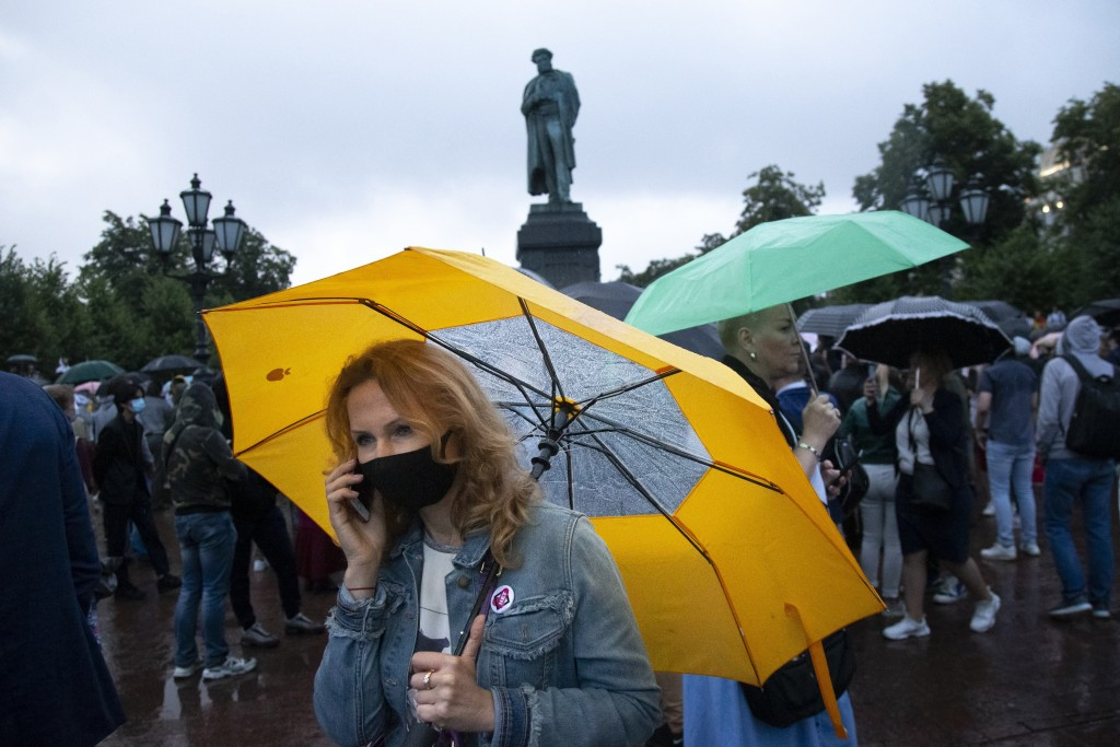 People with umbrellas gather during a rally to cancel the results of voting on amendments to the Constitution in Pushkin square with the statue of Ale...