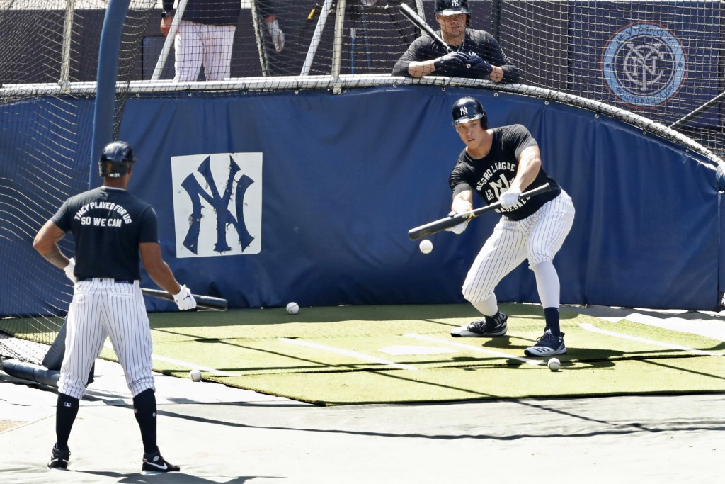 New York Yankees Aaron Hicks, left, and Luke Voit, above right, watch as Aaron Judge begins his batting practice with a bunt at Yankees summer basebal...