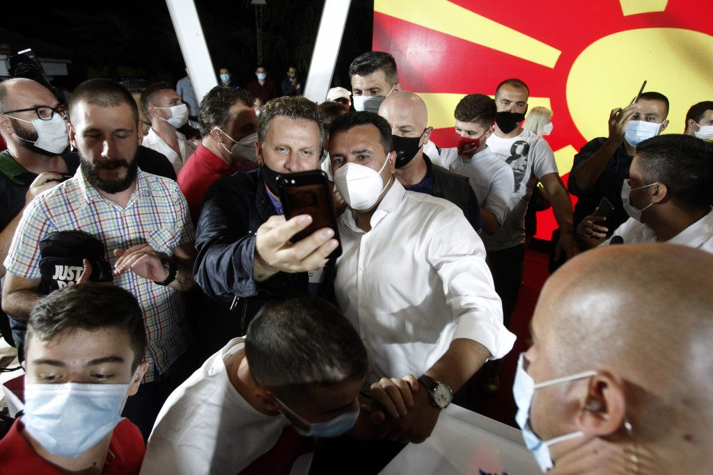 The leader of the ruling SDSM party Zoran Zaev, center right, wearing a mask as he is pose for a selfie after his victory at the North Macedonia gener...