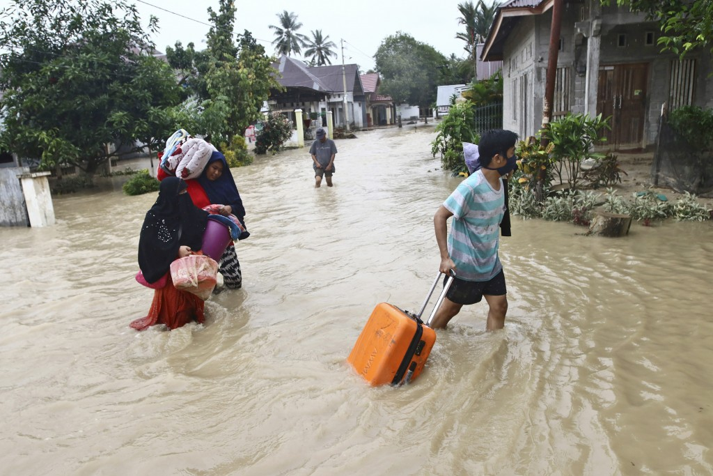 People carry their belongings as they wade through water in an area affected by flash floods in Luwu Utara, South Sulawesi province, Indonesia, Thursd...