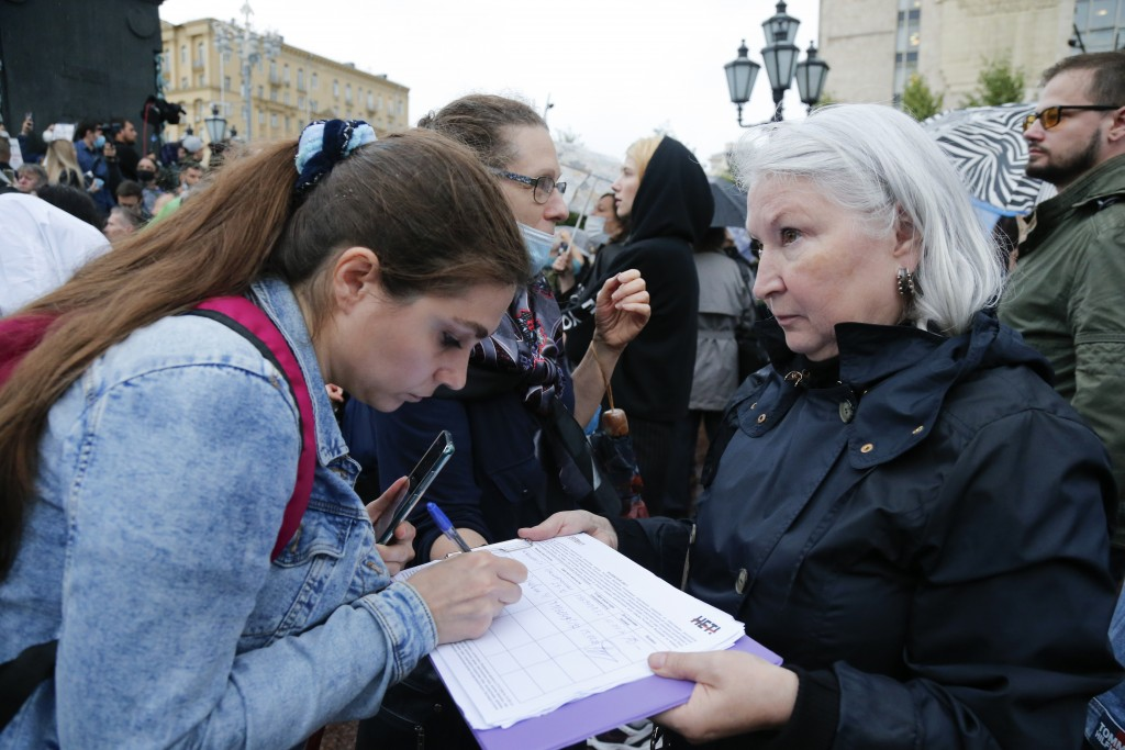 A woman signs a petition to cancel the results of voting on amendments to the Constitution in Moscow, Russia, Wednesday, July 15, 2020. Earlier this m...