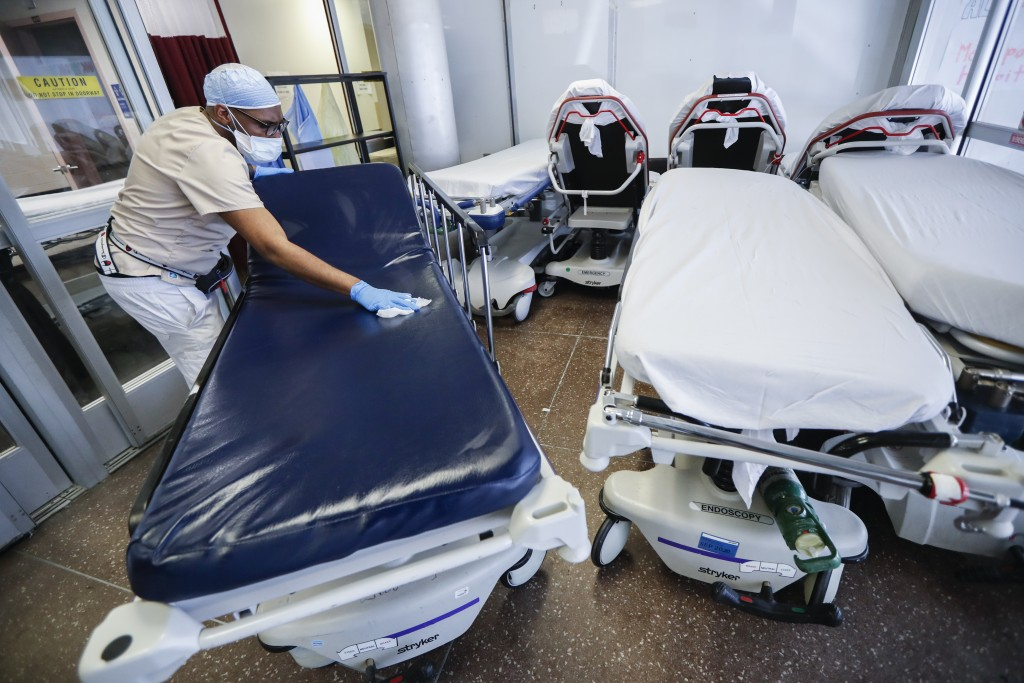 FILE - In this May 27, 2020, file photo, a medical worker wearing personal protective equipment cleans gurneys in the emergency department intake area...