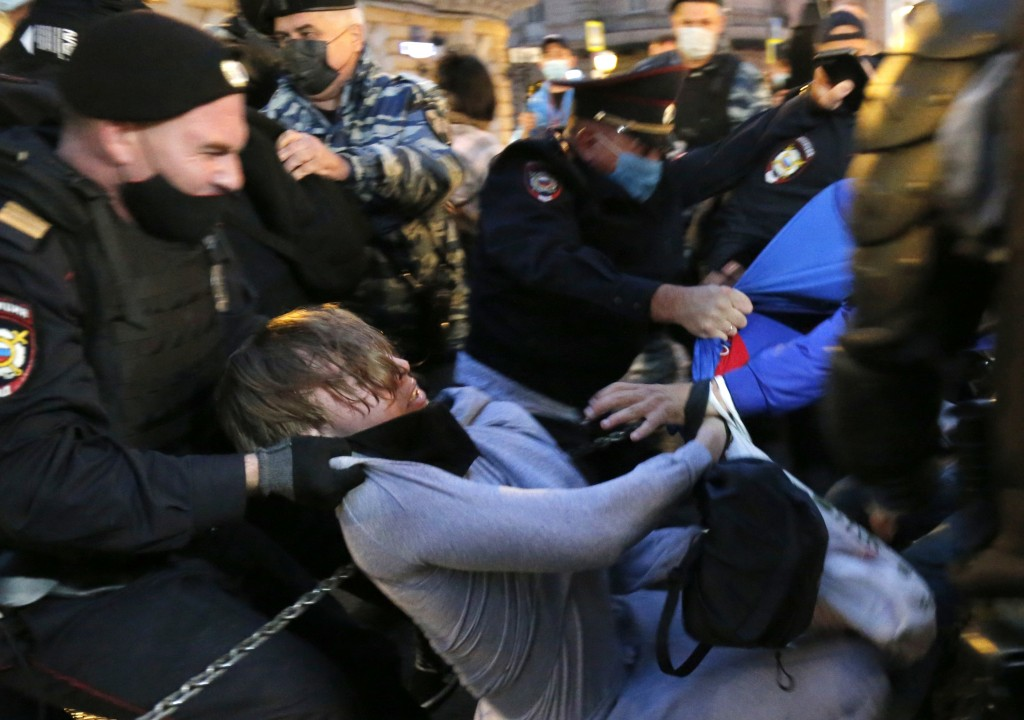 Police officers detain a protester during a rally to cancel the results of voting on amendments to the Constitution in Pushkin Square in Moscow, Russi...