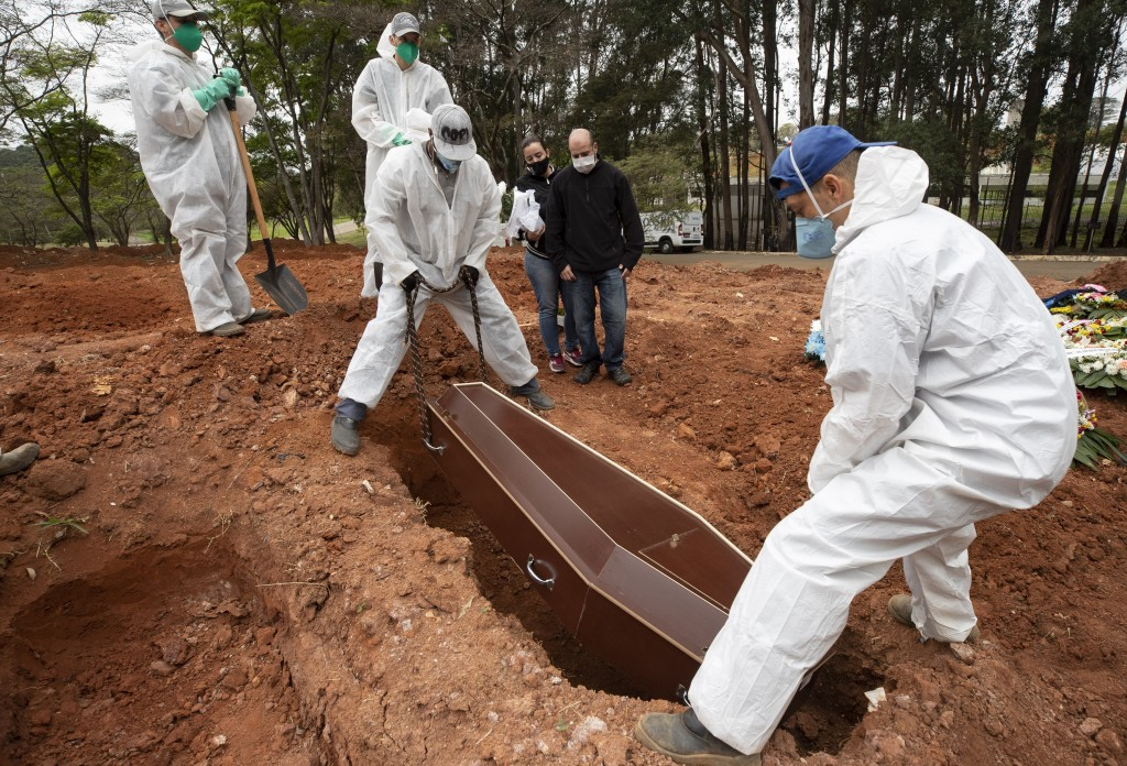 Darick Caverni and his wife Michelle watch as cemetery workers in protective clothing lower the coffin that contain the remains of his 88-year-old  au...