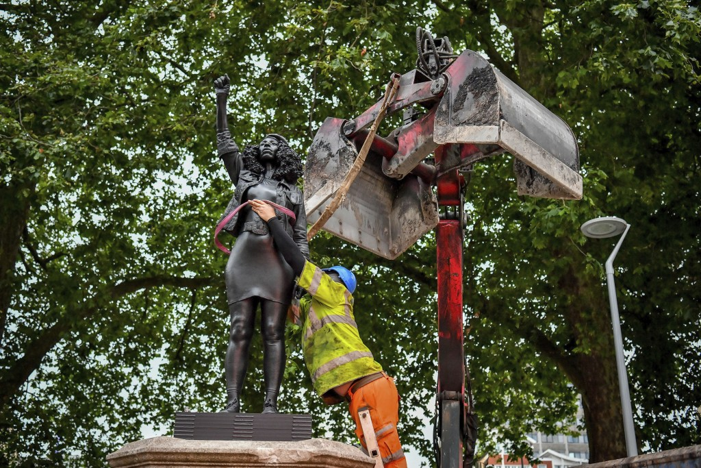 """A contractor uses ropes to secure the statue """"A Surge of Power (Jen Reid) 2020"""" by artist Marc Quinn, which had been installed on the site of the fall..."""