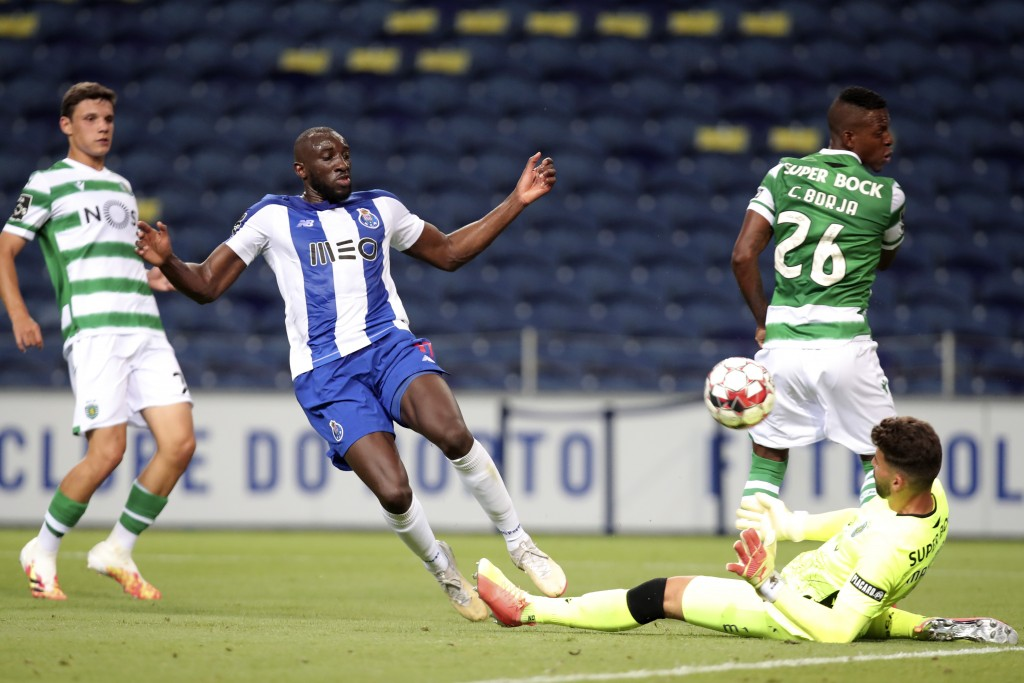 Sporting goalkeeper Luis Maximiano makes a save in front of Porto's Moussa Marega, 2nd left, during the Portuguese League soccer match between FC Port...