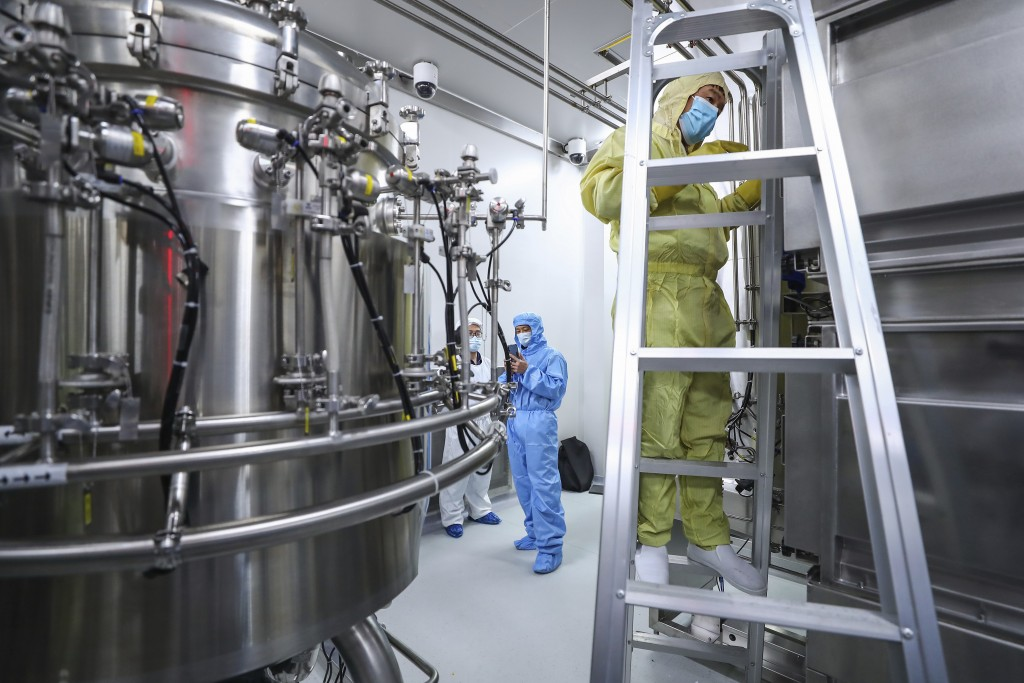 In this April 11, 2020, photo released by Xinhua News Agency, staff members check and clean equipments at a vaccine production plant of SinoPharm in B...