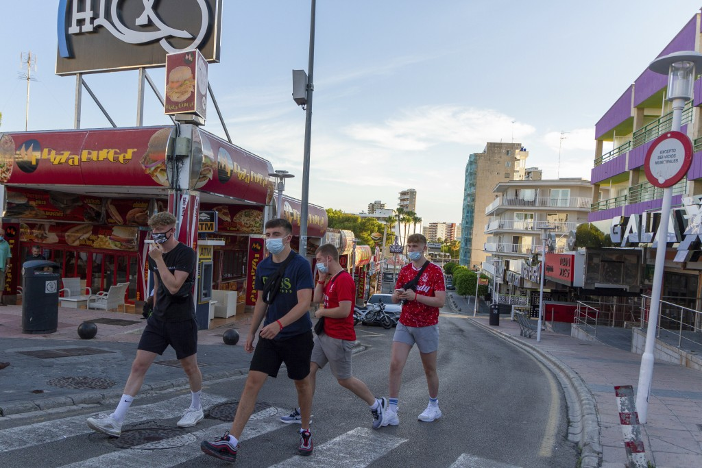 Tourists walk on the street at the resort of Magaluf, in Punta Ballena town, on the Spanish Balearic island of Mallorca, Spain, Wednesday, July 15, 20...