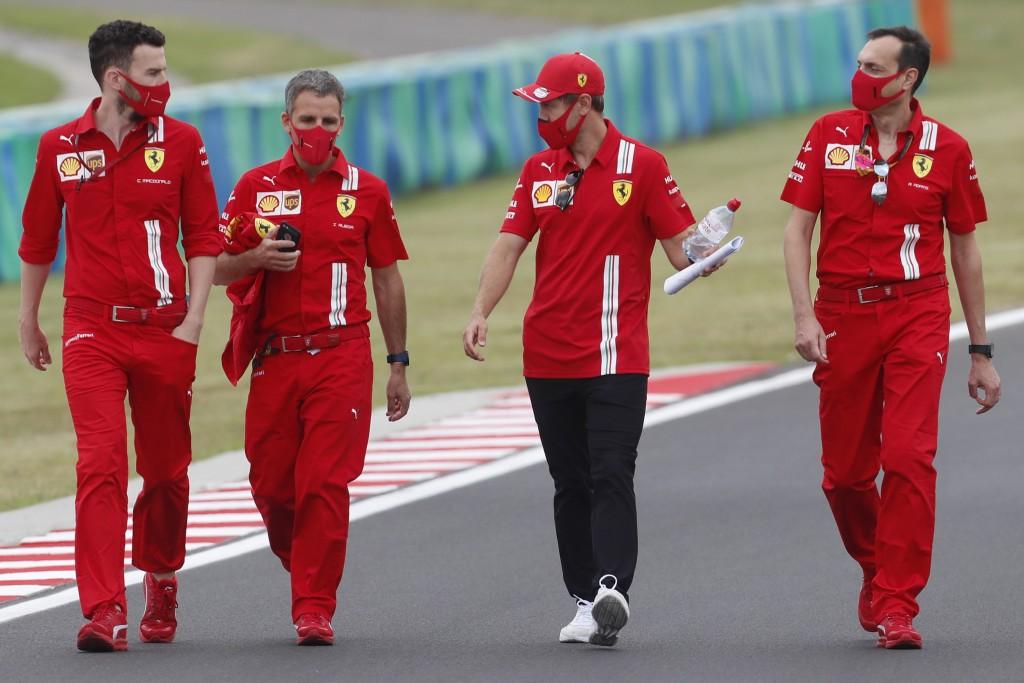 Ferrari driver Sebastian Vettel of Germany, center right, inspects the track with his team at the Hungaroring racetrack in Mogyorod, Hungary, Thursday...