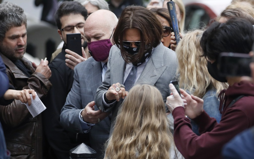 Actor Johnny Depp, centre, is surrounded by fans as he arrives at the High Court in London, Thursday, July 16, 2020. Depp is suing News Group Newspape...