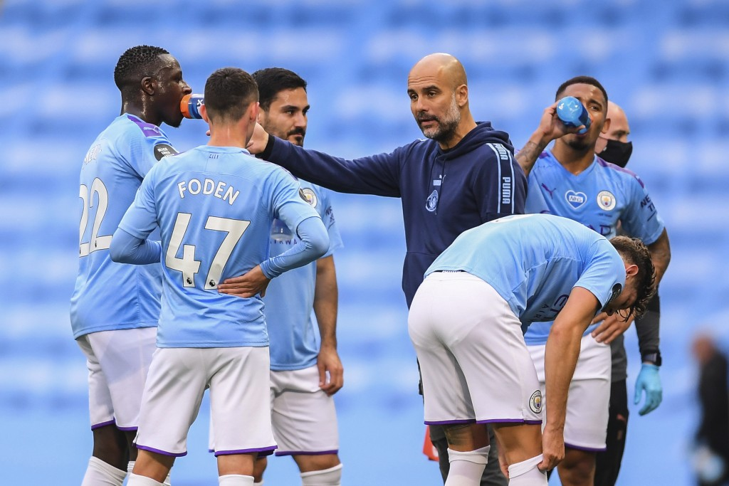 Manchester City's head coach Pep Guardiola, center, talks to his players during the English Premier League soccer match between Manchester City and Bo...