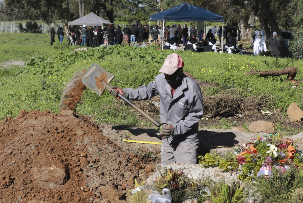 A gravedigger works in the COVID-19 section of the Maitland Cemetary in Cape Town, South Africa, Wednesday, July 15, 2020 as a burial takes place in t...