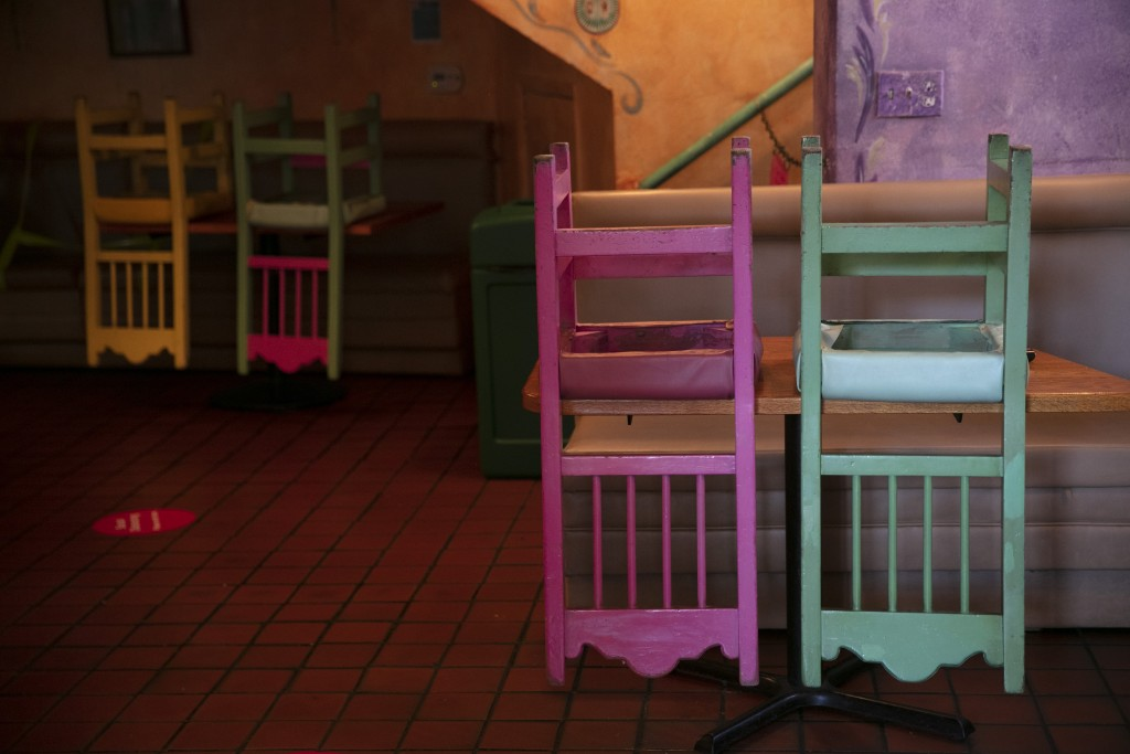 Colorful chairs are flipped over on dining tables at a Mexican restaurant on Olvera Street in Los Angeles, Monday, July 6, 2020. (AP Photo/Jae C. Hong...